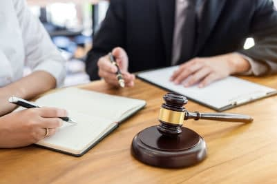 hands writing on paper with gavel in forground